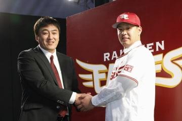 楽天と契約し、石井一久GM(左)と握手する浅村栄斗内野手=1日、仙台市