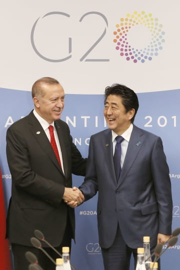 会談前に握手するトルコのエルドアン大統領(左)と安倍首相=1日、ブエノスアイレス(共同)