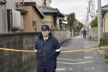 死亡した田村和雄さんの自宅付近で警戒する警察官=2日午前7時43分、静岡県沼津市