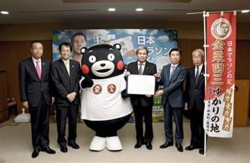 連携協定を結んだ筑波大の永田恭介学長(左から2人目)、蒲島郁夫知事(右から3人目)ら=1日、熊本市中央区