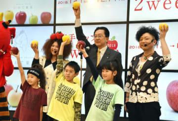 リンゴを掲げてイベントをPRする達増知事(後列中央)ら