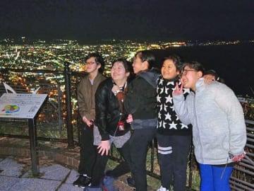 函館の夜景を見ながら笑顔を見せる児童たち(千歳平小提供)