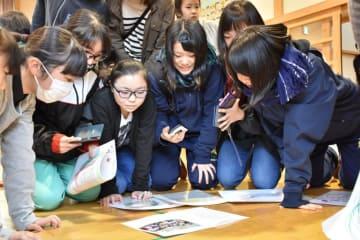 タイムカプセルに入っていた絵や写真を見つめる生徒