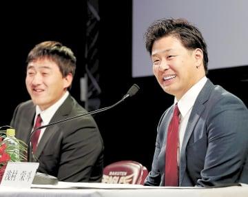 入団記者会見で記者の質問に笑顔で答える浅村(右)。左は石井ゼネラルマネジャー