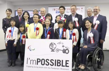 国際パラリンピック委員会のパーソンズ会長(後列右から3人目)と記念撮影に納まる、絵画・作文コンクール受賞者の小学生たち=2日、東京都内
