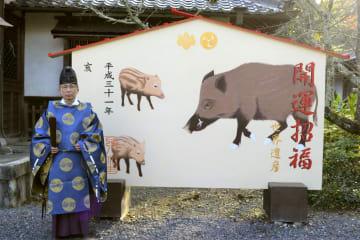 世界遺産・丹生官省符神社で来年のえと「亥」に掛け替えられた大絵馬。左は宮崎志郎宮司=2日、和歌山県九度山町