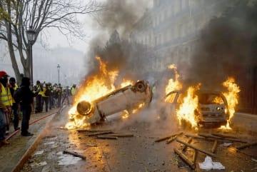 パリの凱旋門近くで放火され炎上する車=1日(共同)