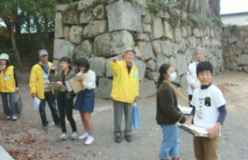 中津城で、石垣や城門に関する説明を聞く「中津少年少女ふるさとクラブ」の児童ら=中津市