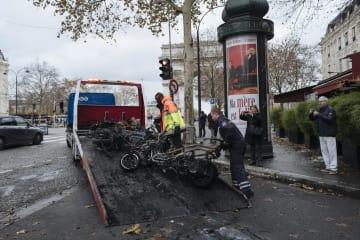 燃料税引き上げ抗議デモから一夜明け、放火されたバイクを片付ける作業員=2日、パリ(AP=共同)