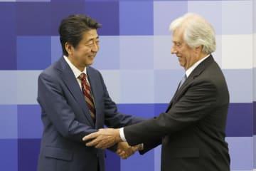 共同記者発表を終え、ウルグアイのバスケス大統領(右)と握手する安倍首相=2日、モンテビデオ(共同)
