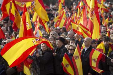 スペインの極右政党ボックスの集会で、国旗を振る人々=1日、マドリード(AP=共同)