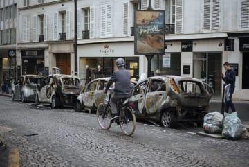2日、パリの凱旋門近くに放置された焼け焦げた車(AP=共同)