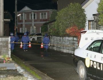 銃弾のようなものが撃ち込まれた住宅(左奥)の周辺を調べる捜査員=4日午前1時23分、富山市