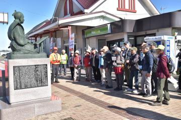 JR高萩駅前の赤水像の前で説明を受ける参加者=高萩市高萩