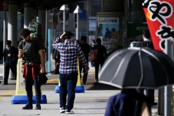 季節外れの暖かさに日傘を差して歩く通行人=4日午後1時ごろ、徳島駅前