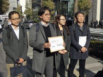 新日鉄住金本社前で、同社に渡す要請書を手にする林宰成弁護士(左から2人目)ら=4日、東京都千代田区