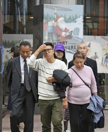 夏日を記録し、上着を脱いで歩く人たち=4日午後、福岡市