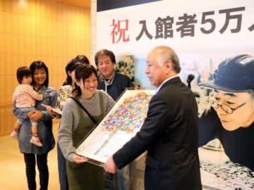 増田市長(右端)から木梨さんの直筆サイン入りのレプリカを受け取る土佐岡さんたち一家