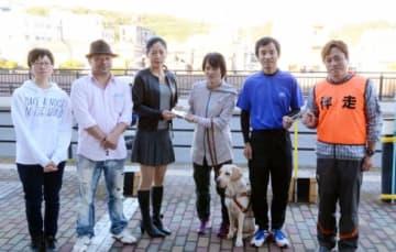 ブラインドランナーズ代表の三雲明美さん(左から4人目)に応援歌「RUNNERS」のCDを手渡す「美女&野獣」のTOMOEさん(同3人目)、HIROSHIさん(同2人目)=鹿児島市のハートピアかごしま