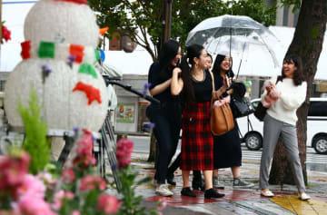県内は季節外れの暖かさとなりノースリーブや半袖姿も見られた=4日午後、宮崎市のデパート前交差点