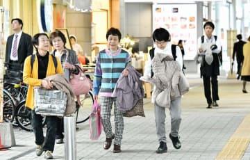 季節外れの暖かさとなり、上着を脱いで歩く人たち=12月4日、福井県福井市のプリズム福井自由通路