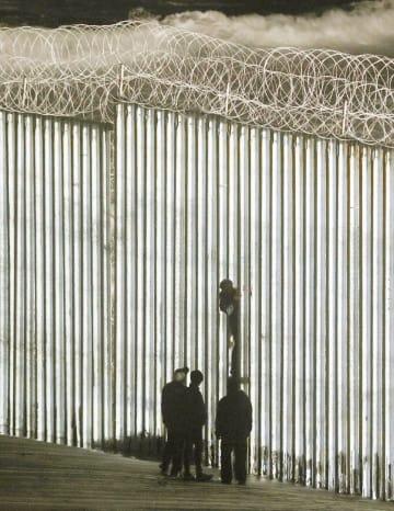 メキシコ北西部ティフアナで、米国境に設けられたフェンスに登る人=1日(共同)