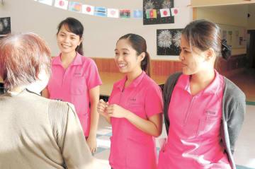 施設利用者と談笑するノエラさん(右端)ら3人のフィリピン人スタッフ。利用者の間でも人気の存在だ=10月中旬、秋田県五城目町