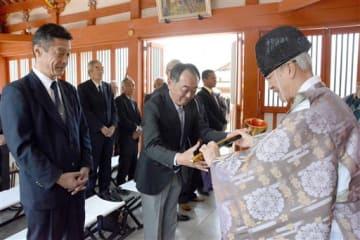 来年の神馬奉納が決まり、金のひしゃくを受け取る高田有志会の宮川和弘代表(中央)=八代市