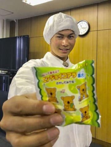 ロッテ浦和工場を訪れ、お菓子を手にするドラフト1位の藤原=5日、さいたま市