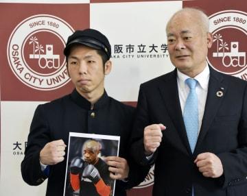 世界戦初挑戦を発表しポーズをとる大阪市立大大学院生でIBFフライ級の坂本真宏選手(左)。右は荒川哲男学長=5日午後、大阪市