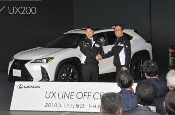 量産が始まったレクサスの新型SUV「UX」の記念式典で、車の前で関係者と握手を交わすトヨタ自動車九州の永田理社長(右)=5日、福岡県宮若市