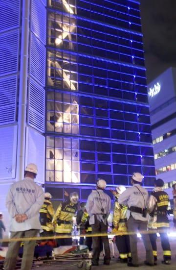 ぼやのあった福岡タワーの前で出火場所付近を見上げる消防隊員ら=5日午後7時、福岡市早良区