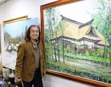 ギャラリーで、市に寄贈する作品について解説する早津剛さん=魚沼市青島