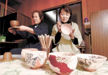成形した器を手にする文夫さん(左)と、絵付けをイメージするひろ子さん=岩沼市北長谷のギャラリー「ひろ窯・茜文麓庵(あかねぶんろくあん)」
