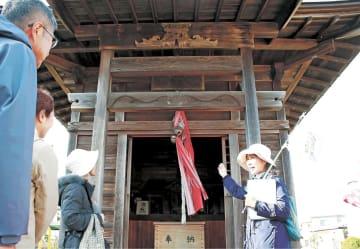 仙台市の旅行会社「たびむすび」が五郎八姫と栗生地区をテーマに企画した街歩きツアーで、薬師堂を案内する佐藤さん(右)。お堂の奥に、謎めく木像が納められている=11月下旬