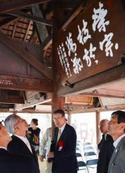 改修工事の終わった絵馬所に掲げられた吉川さんの書を見る参列者(京都市上京区・上御霊神社)