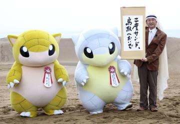 「とっとりふるさと大使」に任命されたポケモンの着ぐるみとPRする鳥取県の平井伸治知事=6日、鳥取市の鳥取砂丘