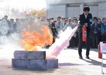 消火器を使って消火訓練を行う職員=県庁