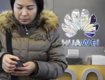 北京にある華為技術(ファーウェイ)の店舗で、スマートフォンを操作する客=6日(共同)
