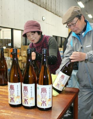 地元産米で造った純米焼酎の瓶詰め作業をする「青山唐変木の会」のメンバーら