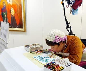 口に色鉛筆をくわえ、色を重ねて絵を制作していく森田さん=6日、大阪市北区の大阪アメニティパークOAPタワー