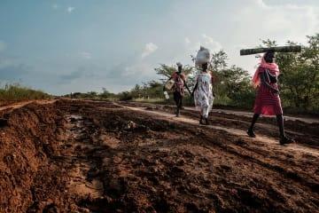 キャンプ外で食糧などを調達するため、長距離を歩く国内避難民の女性ら (南スーダン北部ベンティウで2017年9月27日撮影、資料写真)© Peter Bauza