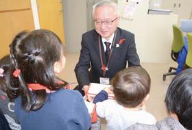 子どもたちから寄付金を受け取る米野事務局長