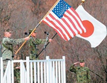 県内で初めてオスプレイを使用する日米共同訓練が始まった。それぞれの国旗を掲げる隊員=7日午前11時1分、日出生台演習場