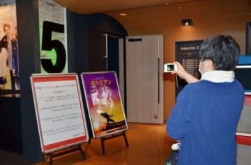 応援上映が行われるシアターの前で写真を撮る人=7日、鹿児島市の鹿児島ミッテ10