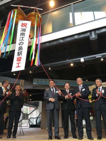 くす玉を割って改修工事の完成を祝う尾渡社長(右から3人目)ら=湘南江の島駅