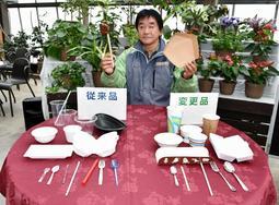 プラスチック製(左)から紙や木、ステンレス製に変わった食器と佐藤哲也園長=神戸市中央区港島南町7
