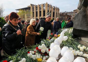 7日、アルメニア北部ギュムリで、大地震30年の犠牲者追悼イベントで花をささげる人たち(タス=共同)