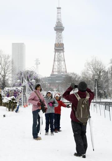 雪化粧した札幌・大通公園で記念撮影する観光客=8日午前、札幌市中央区