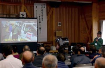 熊本地震時の写真を示しながら話すNPO法人日本防災士会・県支部の宮下正一支部長(右)=宇土市